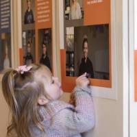 A little girl points to a photo in the exhibit